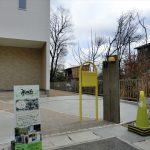 アーチ型のスリットが可愛い駐車スペース&ポップな黄色のポストとナチュラルな機能門柱